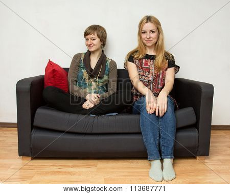 Two Yong Women Are Sitting On The Sofa