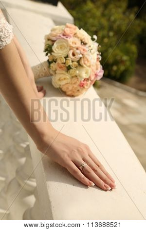 Bride's Hands With Wedding Ring And Bouquet Of Flowers