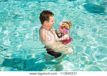 Active Father Teaching His Child Girl To Swim In Pool . Summer Vacations And Sport Concept