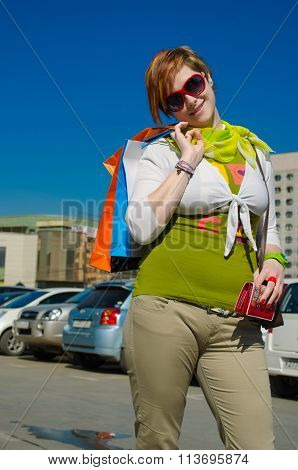 Young Beautiful Woman With Bags After Shopping In The Parking
