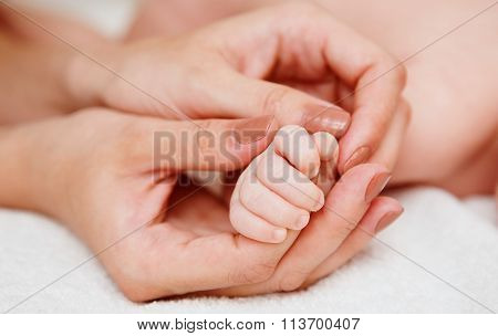 Baby holding mother finger
