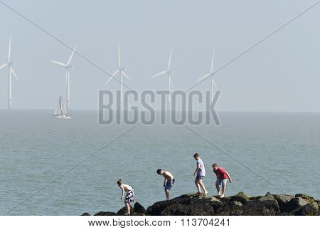 Four boys climbing over rocks at the seaside