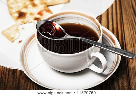 Close-up of a cup of tea, some dry loaves and strawberry jam on a  wooden background in the horizont