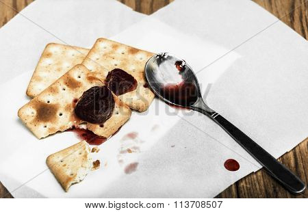 Close-up of a spoon with strawberry jam and some dry loaves on a  wooden background in the horizonta
