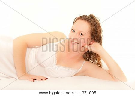Young Woman Lying On Bed Wearing Nightdress
