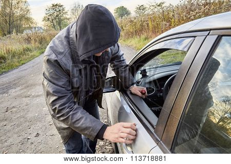 Hooligan breaking into car