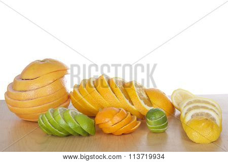 sliced citrus lined up in stacks on light brown wood table with a white background