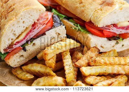 Fried Potatoes And Sandwich With Lettuce, Slices Of Fresh Tomatoes, Salami, Hum And Cheese.