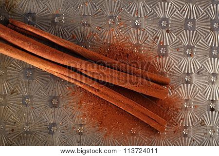 Cinnamon Sticks with Cocoa Powder on old backing metal background