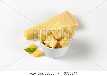bowl and wedge of fresh parmesan cheese on white background
