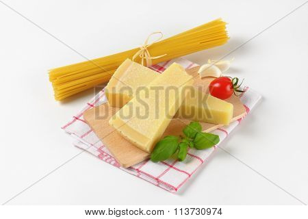 wedges of fresh parmesan cheese, vegetable garnish and bundle of raw spaghetti on wooden cutting board