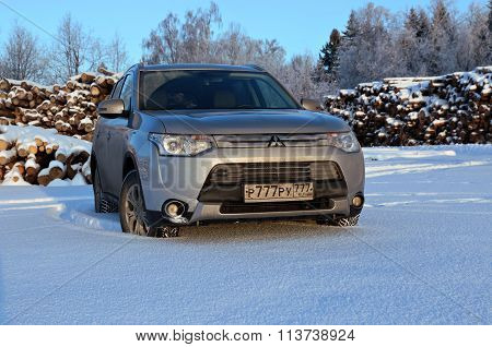 Silver Mitsubishi Outlander Car On The Snow Field On A Background Of Harvested Tree Trunks