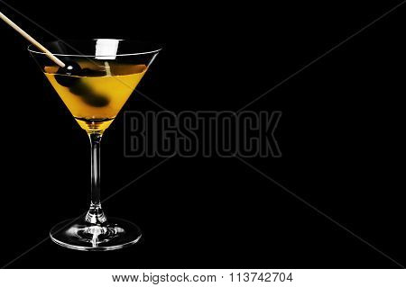 Close-up of martini with black olives on black background
