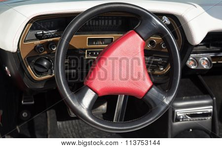 Red steering wheel on an old classy car