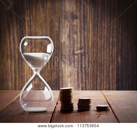 Hourglass with coins on wooden table on wooden background