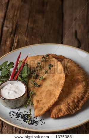 Pasties with garlic sauce and greens on a plate