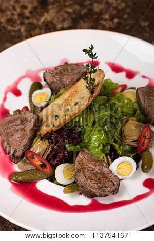Salad with meat, lettuce, quail eggs, pickled cucumbers, red pepper sauce