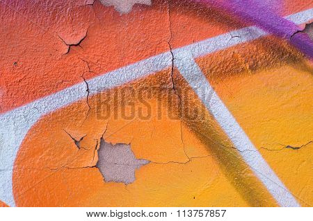 Closeup Of A Peeling And Cracked Wall With Ornage, Violet, And White Spray Drawings