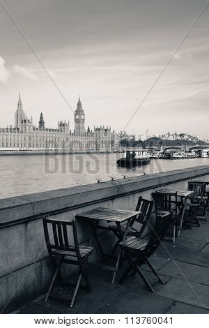 Chairs at waterfront of Thames River with Big Ben and House of Parliament in London.