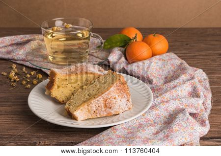 Slices of clementine cake with powdered sugar topping and cup of chamomile tea. Cake on a plate with fresh clementines on wooden board.