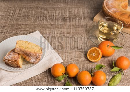 Slices Of Clementine Cake With Powdered Sugar Topping And Cup Of Chamomile Tea. Cake On A Plate With
