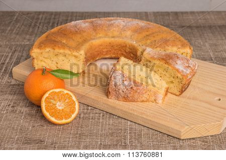 Slices of clementine cake with powdered sugar topping. Cake on a board with fresh clementines on wooden board.
