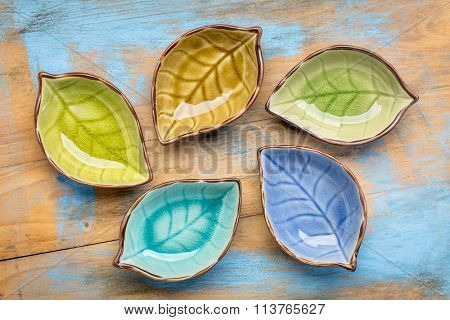 a set of empty, leaf shaped, ceramic side dish bowls against grunge painted wood