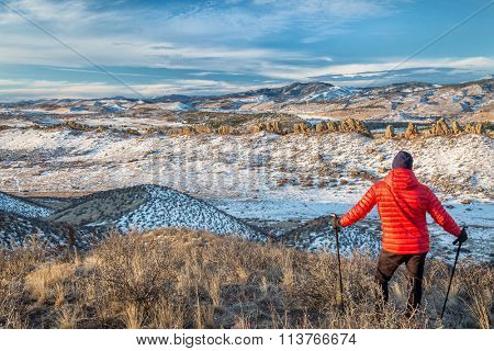 senior male hiker enjoying a view of rock formation at foothills of Rocky Mountains - winter scenery at Devil's Backbone Open Space near Loveland, Colorado