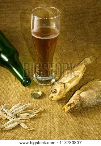 image of the bottle a mug of beer and dry fish closeup