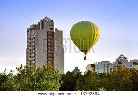 Green balloon over the forest and houses