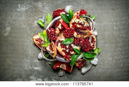 Pieces Of Ripe Pomegranate With Leaves And Ice In A Bowl.