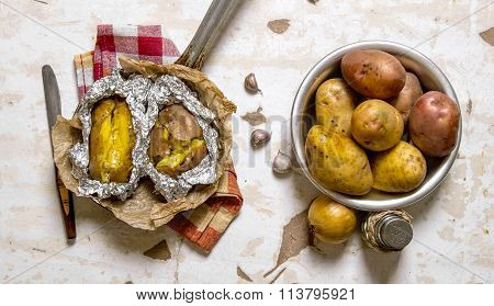 The Concept Of Baked Potato In Foil On An Old Rustic Table .