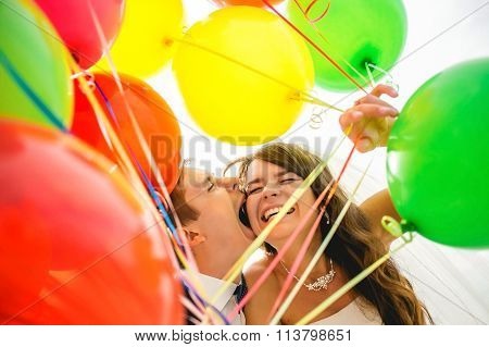 Bright love. Cheerful young wedding couple holding hands and smiling while walking outdoors with col