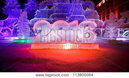 Happy new year 2016 written with ice letters, sculptures in the park beautiful illumination at night
