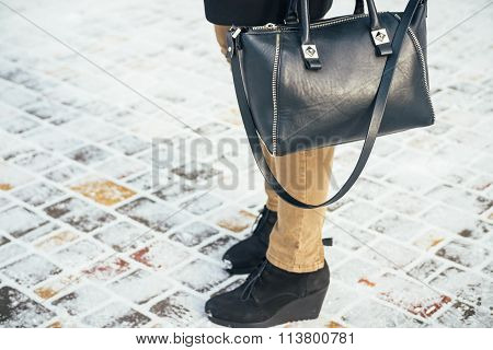Women Standing On A Snow-covered Sidewalk With Handbags, Close-up