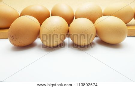 Eggs on wooden board and white floor. Space for texts. Selective focus on front row.