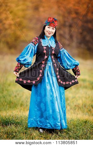 Cheerful beautiful girl in national dress smartly blue with ornaments and embroidery.