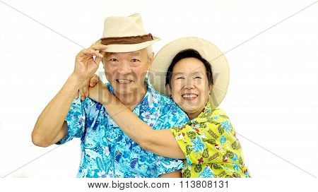 Happy Asian Senior Couple Hugging Happily Wearing Hat Ready For Holiday Trip