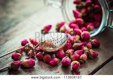 Rose Buds, Tea Strainer And Glass Jar On Rustic Wooden Table. Retro Styled. Selective Focus.