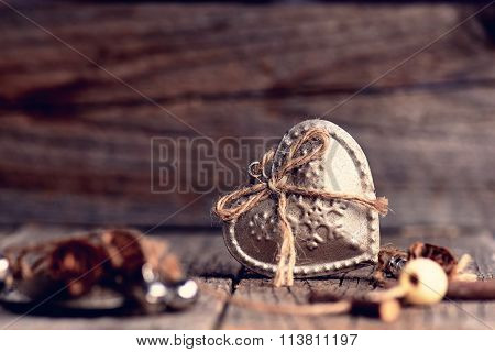 Silver heart on a wooden table with decorations. Valentines day. Love. Gift on a natural background.