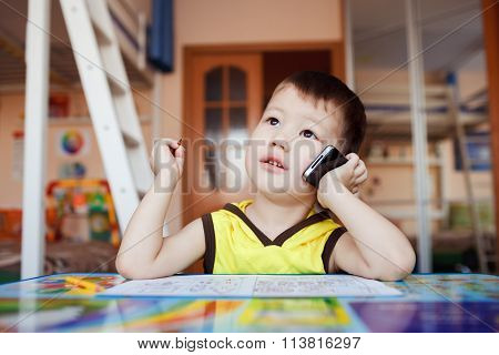 Little boy takes an important call on his cell phone, while drawing at home with felt pens.