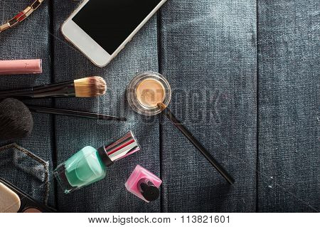 Female Handbag With Cosmetics And Mobile On Jeans Background