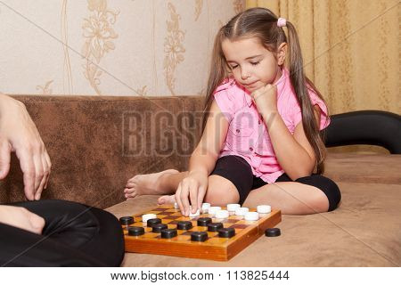 Girl Playing Draughts With Her Mother