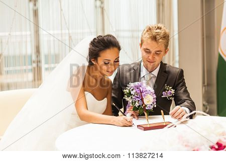 Wedding ceremony. Bride and groom leaving their signatures