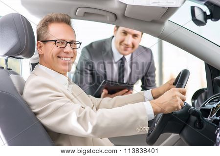 Sale assistant showing car to customer