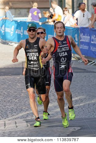 STOCKHOLM SWEDEN - AUG 23 2015: Tough fight between three running triathletes Gregory Billington in the lead in the sunshine in the Men's ITU World Triathlon series event August 23 2015 in Stockholm Sweden