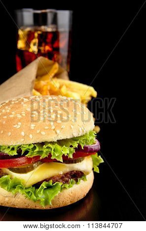 Cropped Image Of Cheeseburger,french Fries,glass Of Cola On Black