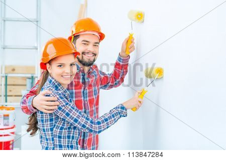 Nice loving couple pointing walls