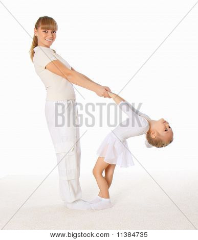 The Young Mom And Her Little Daughter Doing Exercises Together