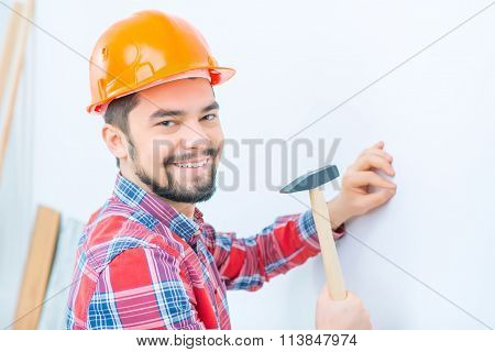 Pleasant man knocking in the nail
